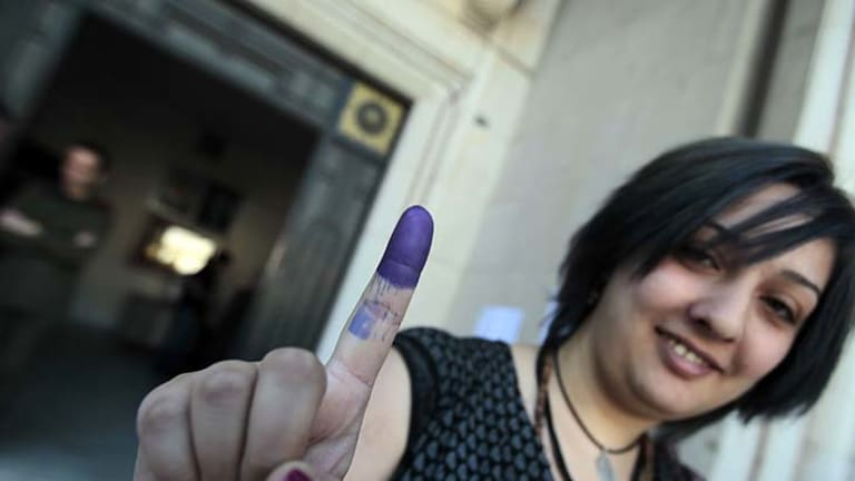 A Syrian woman shows her ink dipped finger after casting her vote in the parliamentary elections at a polling station in Damascus.