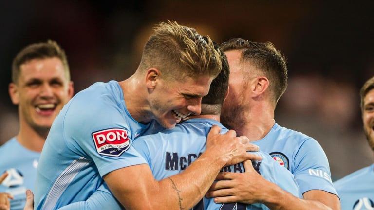 Harrison Delbridge celebrates with Ross McCormack after McCormack scores a goal for Melbourne City.