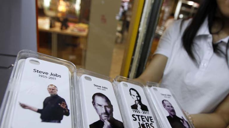 In loving memory ... a shop assistant in Shenzen displays newly released covers for the the iPhone 4.
