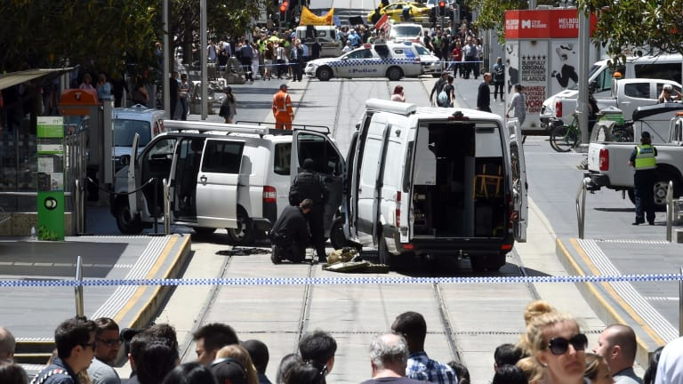 The bomb squad inspect a suspicious package wedged found while workers were removing the tributes to the Bourke St mall victims.