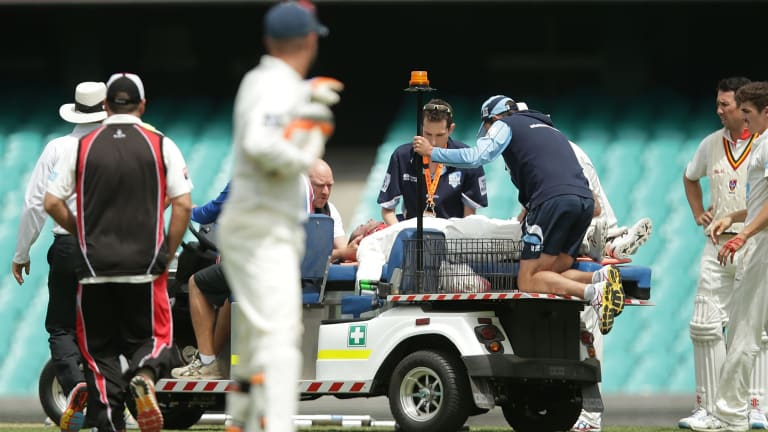 Phil Hughes is stretchered off the SCG.
