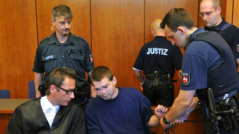 Guilty ... a police officer takes off the handcuffs of defendant Jan O, whose face has been blurred in accordance with German law.