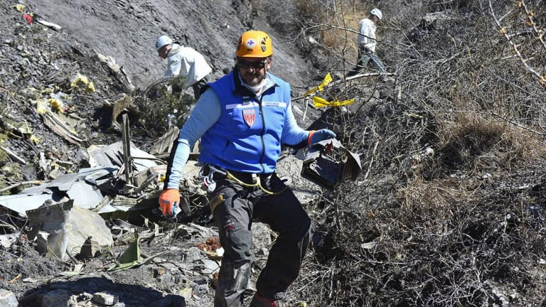 Recovery operation: A French gendarme makes his way through debris of Flight 4U 9525 in the French Alps.