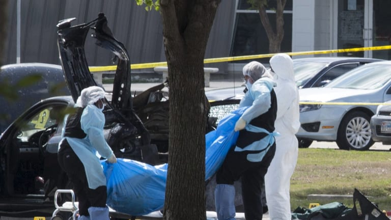 The bodies of gunmen Elton Simpson and Nadir Soofi are removed from behind a car during an investigation by the FBI and local police in Garland, Texas.