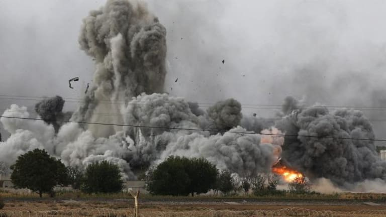 Smoke, debris and fire rise in Kobane after an air strike by the US-led coalition.