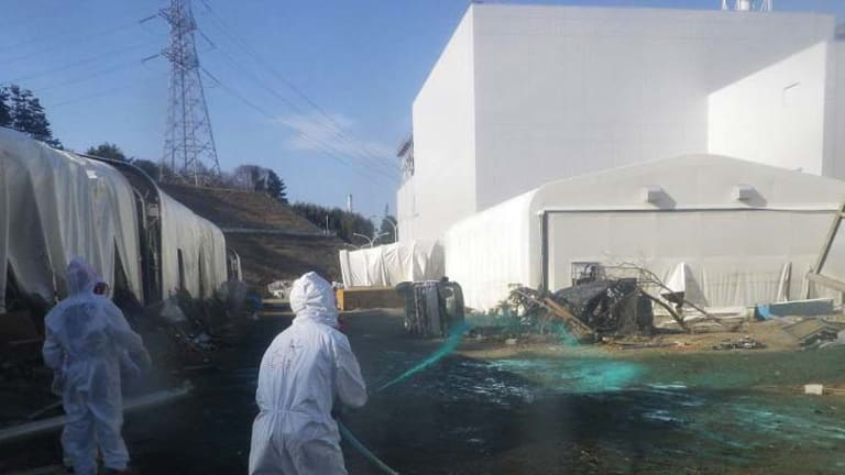 Tokyo Electric Power Co. workers spray adhesive synthetic resin over the ground at the Fukushima Dai-ichi nuclear power plant.