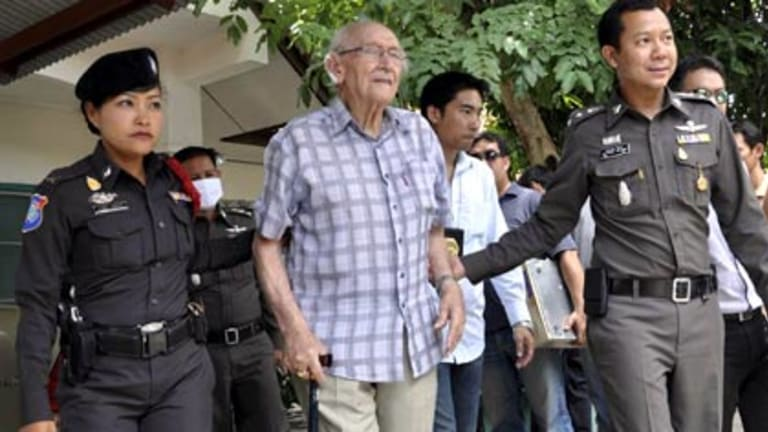 West Australian Karl Kraus, 90, is escorted by Thai police after his arrest.
