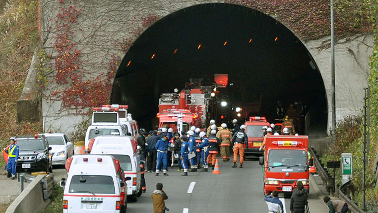 Police officers and firefighters gather at the exit of the collapsed Sasago Tunnel on the Chuo Expressway in Otsuki, Yamanashi Prefecture, in central Japan. Several people were feared trapped inside.