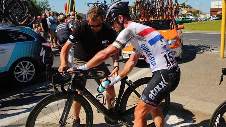 Change of bike: Mark Cavendish hops back on.