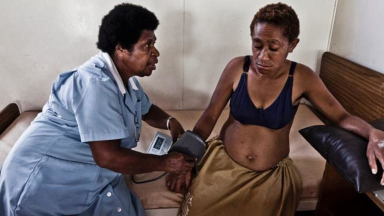 Baby worries: A nurse at the Port Moresby antenatal clinic examines a five-month-pregnant woman attacked by her husband who kicked her in the stomach and threw her out of the house.