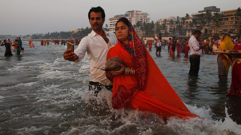 A man takes a selfie with his wife as she offers prayers to the Sun at the Arabian Sea during Chhath Puja festival in Mumbai, India.