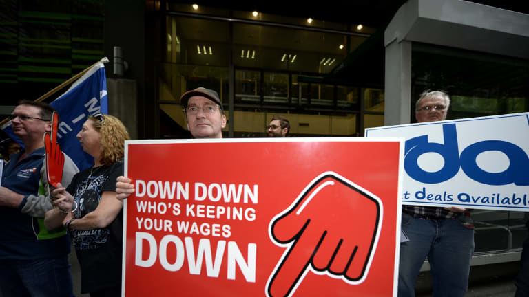 Meatworkers union members protest outside the shop assistants' union over its wages deal with Coles.