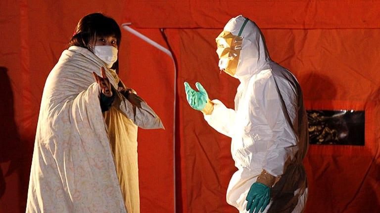 An official in protective gear talks to a woman evacuated from the area near the Fukushima Daini nuclear plant.