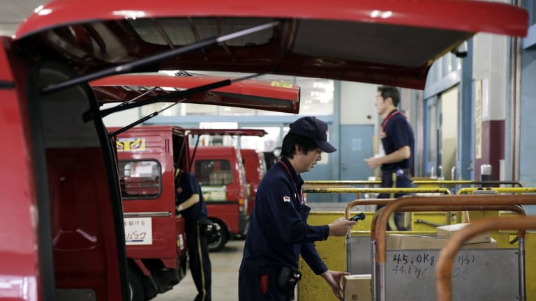 An employee, center, scans a parcel before loading the package onto a van at a Japan Post Co. post office in Tokyo, Japan