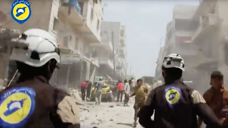 Syrian Civil Defence White Helmets workers run after airstrikes and shelling hit Aleppo.