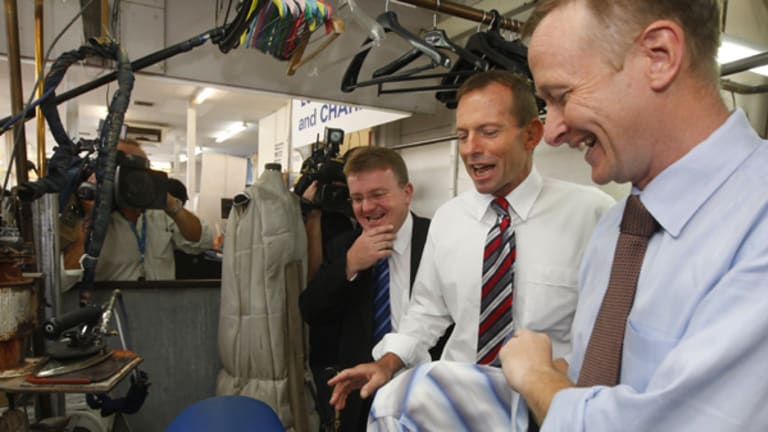 Member for Dunkley Bruce Billson and opposition leader Tony Abbott during a visit to the Bells Foxy Dry Cleaners in Queanbeyan owned by Jason Webb, right.