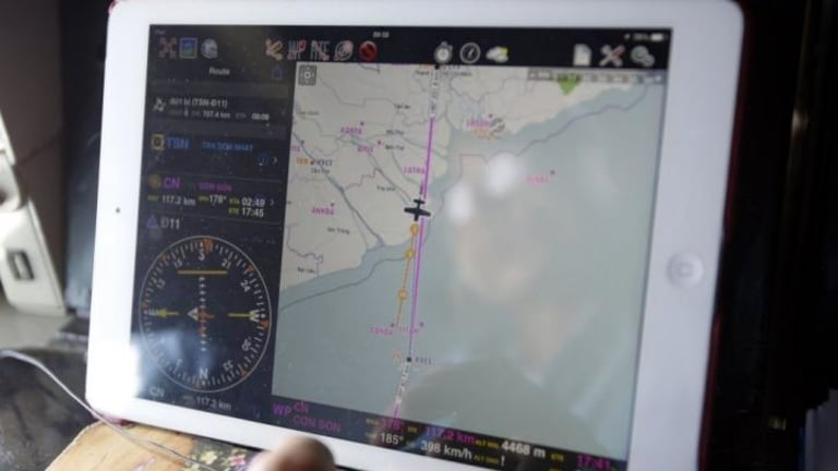 The search continues ... Military officer Ngo Ngoc Dong is seen reflected in a map on an iPad showing the path of the Vietnam Air Force search and rescue AN-26 aircraft.