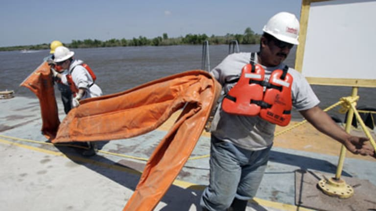 Workers carry oil booms across a dock in Venice.