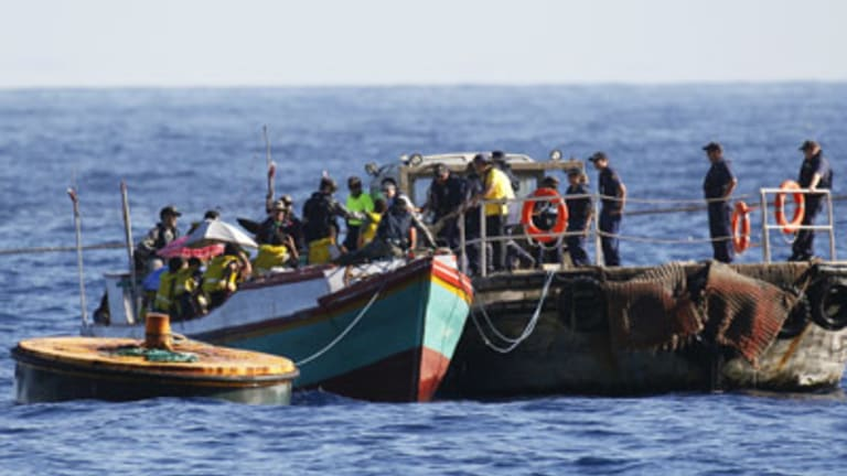 Customs officials take people from a vessel intercepted just off Christmas Island on Thursday.