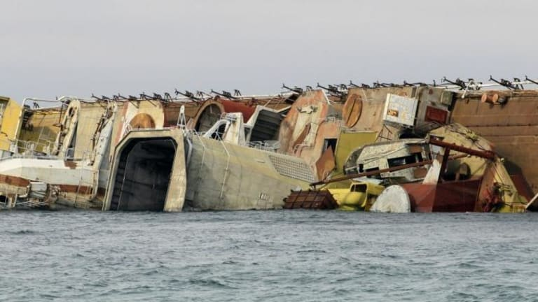 The decommissioned Russian anti-submarine vessel Ochakov lies on its side off the Black Sea shore, where it was sunk to block Ukrainian naval vessels from entering the sea from their base.