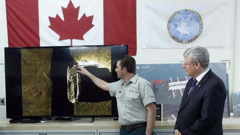Canada's Prime Minister Stephen Harper (right) listens as Parks Canada's Ryan Harris talks about an image showing one of two ships from the lost Franklin expedition, in Ottawa.