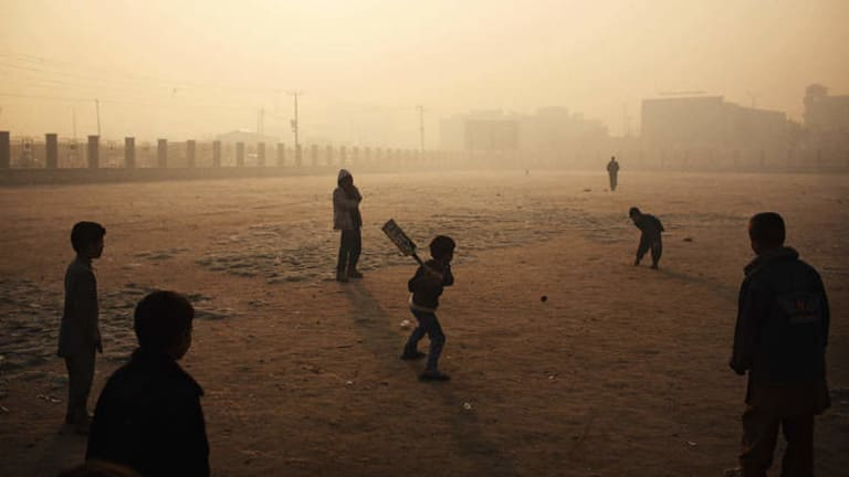 Pitched battle: Boys play cricket on a hazy winter's morning in Kabul.