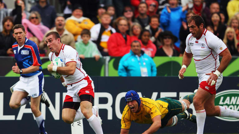 Vladimir Ostroushko brakes past Nathan Sharpe to score for Russia against Australia. It was one of eight tries they scored in the tournament.