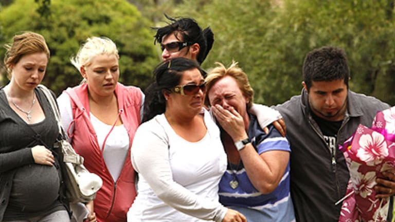 Distraught friends and family gather at the scene of yesterday's single-vehicle crash in Mill Park, which left five teenagers dead and injured a girl.