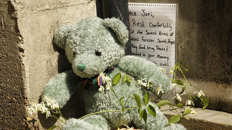 Horrific death ... a stuffed bear and a handwritten note are seen outside the home where Jori Lirette was found decapitated.