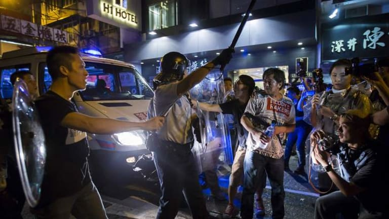 A riot police officer holds a baton as he confronts Occupy Central protesters.