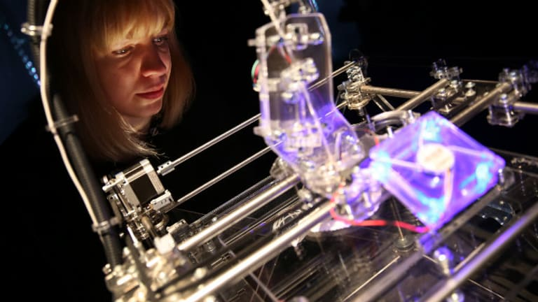Installation designer Susana Soares looks at a 3D printer at the 'Insects au Gratin' exhibition at the Wellcome Collection in London.