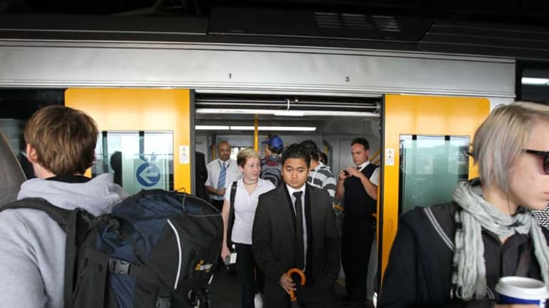 Delays ... passengers alight from a Waratah train at Circular Quay. The financially troubled project is 18 months behind schedule.