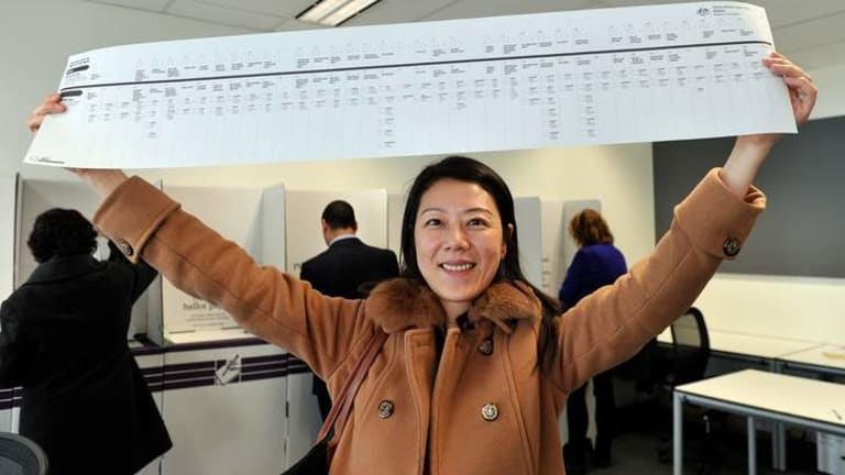 Sumin Sun holds the Senate ballot paper which is just over a metre long.