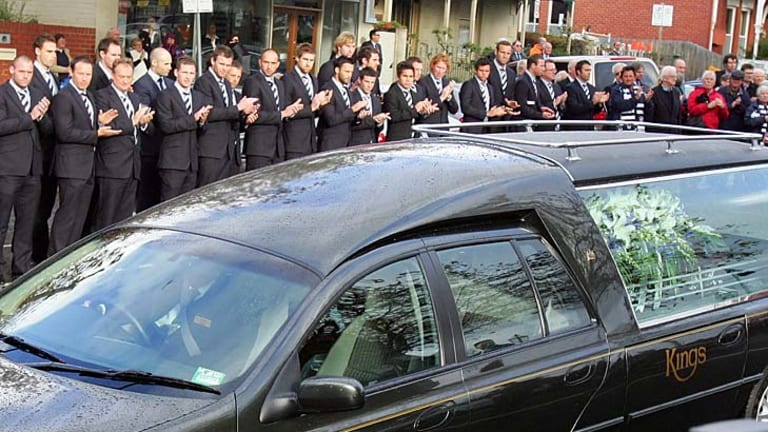 Geelong players form a guard of honour as the hearse leaves after Bob Davis' funeral.