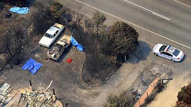 Bodies lie in front of a house that was razed to the ground on the Whittlesea-Yea Road.
