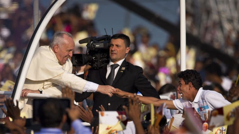 Ecstatic welcome ...  A devotee stretches out his hand to touch Pope Francis.
