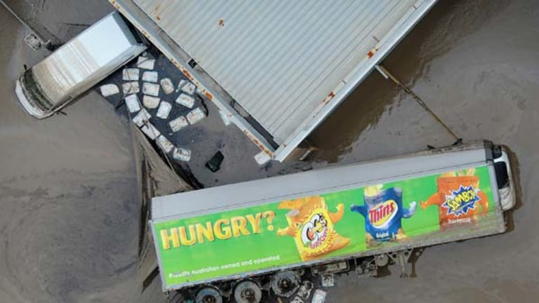 A food transport trailer lays on its side in mud as the floodwaters recede in the Brisbane industrial area of Rocklea on January 14.