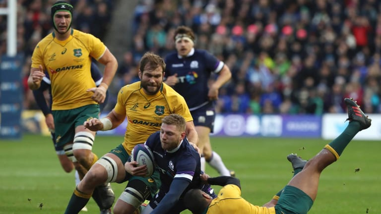 Scotland's Finn Russell is brought down by Australian players.