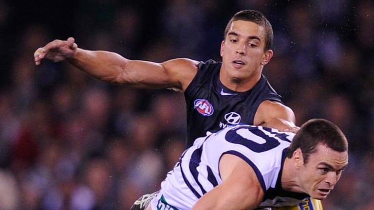 On the run: Geelong defender Matthew Scarlett gives Carlton's Andrew Carrazzo the slip.