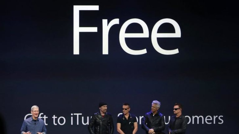 Free for all: Apple CEO Tim Cook and the band onstage at the product launch where the biggest giveaway in the history of rock was announced.