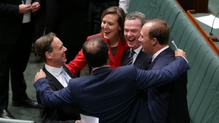 Environment Minister Greg Hunt is congratulated by colleagues after Carbon Tax Repeal Bills pass the Lower House. The Anglican Church has called on the Abbott government to change its policies on climate change.