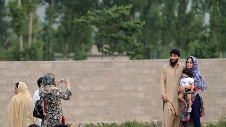 A Pakistani family poses for photographs in front of the final hiding place of al-Qaeda chief Osama bin Laden in Abottabad.