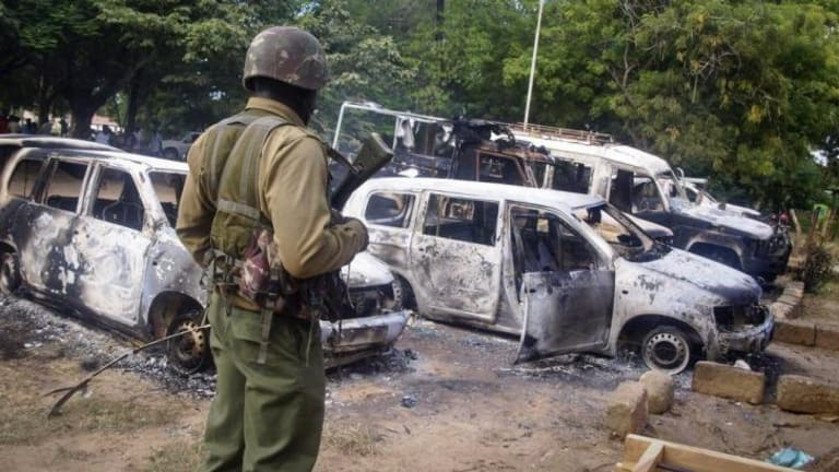 A member of the Kenyan security forces observes the remains of vehicles destroyed by militants