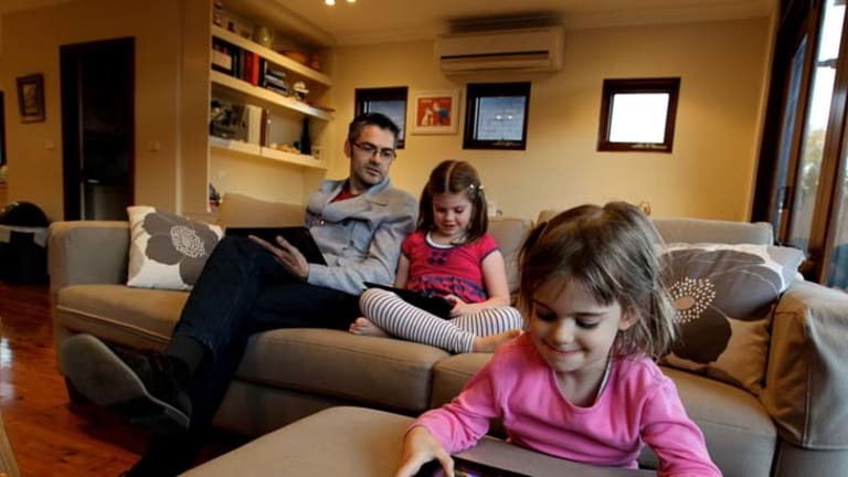 Keep talking ... Andrew Sidwell and his daughters - Hudson, 7, and Lola, 4, using tablets at their home in Maroubra.