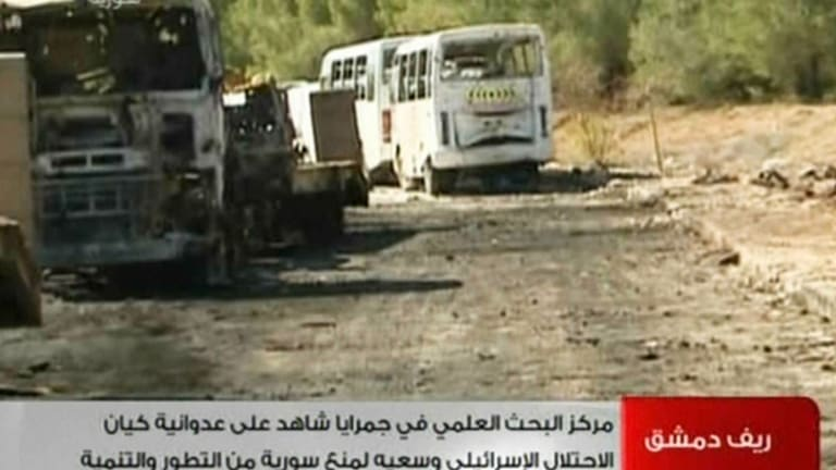 State-run Syrian TV on February 2, 2013 shows damaged vehicles after what Syria said was an Israeli air raid which targeted the Jamraya scientific research base.