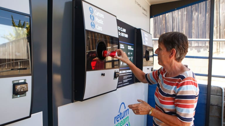 Una Bell loads a can into a Return and Earn reverse vending machine in Granville.
