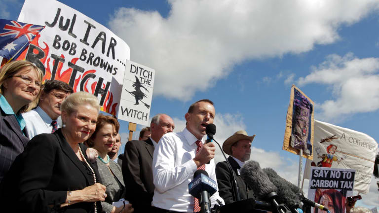 """Then opposition leader Tony Abbott in front of a """"ditch the witch"""" poster, which targeted his election rival Julia Gillard."""
