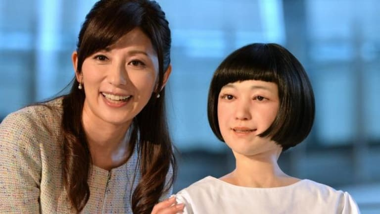 """Japanese announcer Aki Nakata (left) smiles as she poses with a new humanoid robot named """"Kodomoroid"""" at the National Museum of Emerging Science and Technology in Tokyo."""
