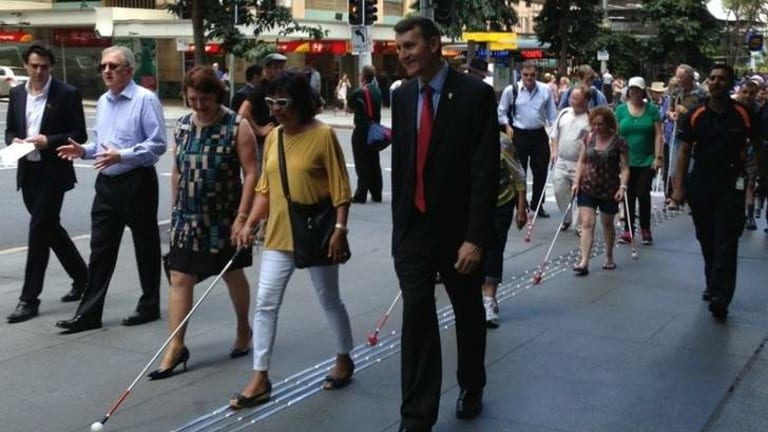 Lord Mayor Graham Quirk tests out the new extension of Brisbane's Braille Trail with some of the city's vision impaired citizens.