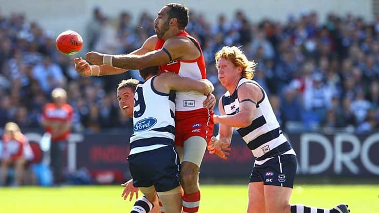 Sydney's Adam Goodes gets a handball away as he is tackled by Geelong's James Kelly at Skilled Stadium.